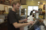Patrick Farrelly(cq) works the register checking out a customer. Jason Shidler (cq) and Patrick...