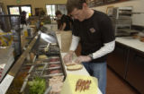 Jason Shidler(cq) works behind the counter making a sandwich for a customer in the deli.  Jason...