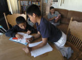 Alex Romero-Olivan, 9, left, reads the Cat in the Hat in English to his adopted brother, Diego...