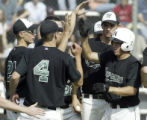 (Englewood, Colo., May 13, 2005) Mike Harpe (right, 7, white helmet) greets his team at home plate...