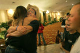 Lance Corporal Mike Ball (cq), 22, with cowboy hat, hugs friends in the lobby of the Holiday Inn...