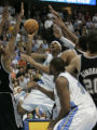 Denver Nuggets Carmelo Anthony drives through a crowd of San Antonio Spurs during overtime action...