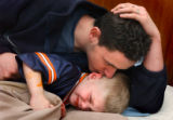 (Vernal, Utah) Jonathan Swain, 21, comforts his wife's child, Stanley Padigimus, 4, who was tired...