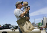 Sean Durant (cq), 24, gives a kiss to his son Zachery Durant (cq), 2, while panhandling on the...