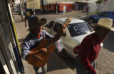 Pedro Chavez, center, of Santiago Papasquiaro, sings and plays guitar along the town streets on...