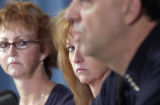 Kelly Young (center), widow of slain police officer Donald Young, listens to  Denver Police Chief...