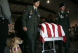 The Honor Guard wheels out the casket for SPC Travis Anderson (cq), while his beloved dog, Daniel,...