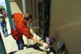 Denver policeman Ed David (cq), red shirt, leaves flowers at a memorial for his friend, Detective...