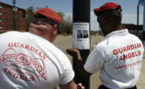 Peter Dempsey (cq), left, and Ted Fowler (cq), right, put up wanted posters for Roul Garcia-Gomez...