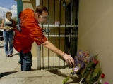 Denver policeman Ed Davis (cq), red shirt, leaves flowers at a memorial for his friend, Detective...