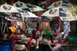 Beer umbrellas and revelers celebrating Oktoberfest are reflected in a window on Larimer Street in...