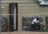MJM1169  A man reads a book inside the  fenced in confines of Camp George West Monday afternoon in...
