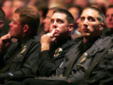 Officers from the Aurora Police department watch a montage of photos of their friend and...