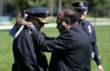 Aurora Police Captain Jerry Hinkle (cq) from District 3 (left) prays with the Bishop Acen...