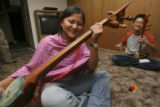 Tenzin Palzom, left, with larger instrument, shares a laugh during rehearsals, with fellow...