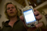 Bill Twyford (cq) of Bailey, Colo., holds a PocketPC phone displaying a message sent by his...