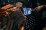 Colorado Football fans get ready to flip a burger at a tailgate party's makeshift spatula, a...