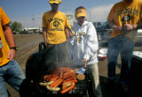 Dara Vandenberger (CQ) of Erie, Colo., gets ready to flip a burger with her tailgate party's...