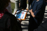Friends hold a photo of the deceased after the services. Luz Maria Franco Fierros, (cq), was...