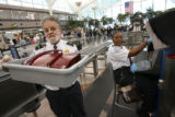 TSA screener Warren Brunner(cq), left, carries a bin containing a purse that his co-worker,...