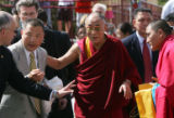 Flanked by security, the Dalai Lama greets a group of Tibetan monks as he walks into the Newman...