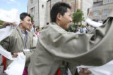Tenzin Loden, left and Tenzin Desel, right, wave prayer flags in welcome of the Dali Lama before...