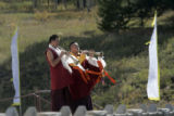On September 17, 2006, two Tibetan monks play horns while the Dalai Lama leaves the Great Stupa at...