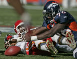 Denver Broncos Kenard Lang reaches for a fumble that was recovered by Michael Myers and caused by...