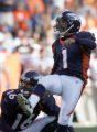 Denver Bronco quarterback Jake Plummer,bottom, as kicker Jason Elam,right, successfully kicks a...