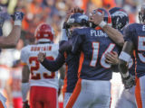 Denver Bronco kicker Jason Elam, left, gets hugged by teammates after Elam made good on a 39-yard...