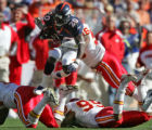 Denver Bronco running back Mike Bell leaps over Kansas City Chief defenders for a one yard gain...