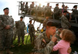 MJM086 2nd Brigade Army Specialist, Christopher Taylor (cq), right center, tries to quiet Zoe...
