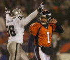 Denver Broncos kicker Jason Elam, #1, leaves the field as Oakland Raiders Bobby Hamilton, #98,...
