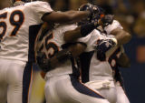 Teammates mob Denver Broncos linebacker Al Wilson in the end zonein the second quarter at the...
