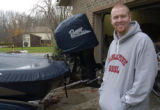 SPECIAL TO THE ROCKY MOUNTAIN NEWS- Rockies' pitcher Aaron Cook stands next to his bass boat at...