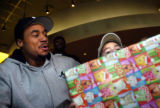 12/07/2004 Denver-Ryan Bonine, 3, Lakewood, picks up a gift given to him by Denver Bronco Kyle...