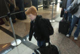 (Denver, Colo., November 24, 2004) Quinn Labarge carries his bag in the checkout line at DIA...