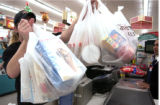 (Denver, Co.,  Nov.  24, 2004)  Russ Kettle packs up groceries as he finishes his grocery list at...
