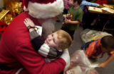 (Denver, Colo., December 16, 2004) Rien Hogan (cq), 3, gives a hug to Santa Claus, Pat kelly, at...