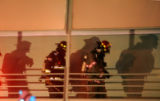 (DENVER Colo., December 5, 2004)  Denver fireman  watch as members of the Denver Coroner's office...