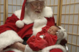 (ENGLEWOOD, Colo., December 4, 2004) Santa gently cradles 3 day old Andrew Michael Walford after...