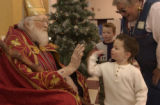 (LITTLETON, Colo., December 4, 2004) Matthew Gust,3, high five's St. Nick as his brother, Corey...