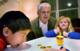 (Denver, Colo.,12/7/2004) (L-R) Ryan Beckett,8 (red) watches his dreidel  as he plays the...
