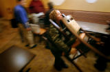 (DENVER, Co., SHOT 11/16/2004) Rioja server Beth Mikash of Denver carries a pair of chairs into...