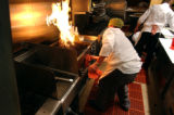 (DENVER, Co., SHOT 11/16/2004) Line cook Kevin Chambers of Aurora reacts quickly to extinguish...