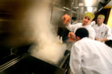 (DENVER, Co., SHOT 11/16/2004) Line cook Kevin Chambers (center, with towels in hands) of Aurora...