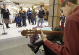 Aurora, Colorado.  November 26, 2004}   Shoppers stop to listen to David Beatty, 15, of Aurora,...