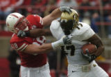 (Lincoln NB, November 26, 2004)  Lawrence Vickers tries to fight through a tackle by Barrett Ruud,...