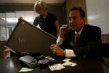 Ed Perlmutter, right, makes a phone call to a potential campaign donor while his deputy finance...