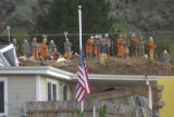 La Conchita 1-12-05 A flag stands at half mast in a front yard. Crews stand atop a portion of the...